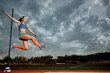 Leinwanddruck Bild - Female athlete performing a long jump during a competition at stadium. The jump, athlete, action, motion, sport, success, championship concept