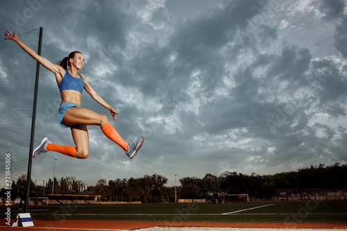 Leinwanddruck Bild Female athlete performing a long jump during a competition at stadium. The jump, athlete, action, motion, sport, success, championship concept