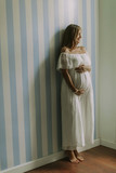 Young pregnant woman standing by the wall - 221851236