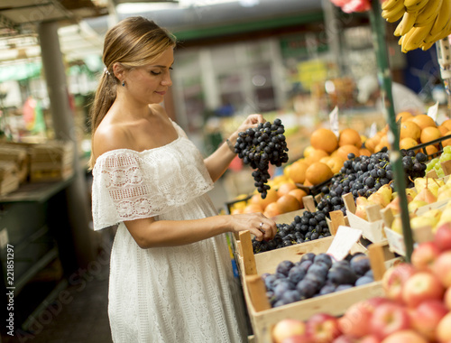 Poster Young woman buying fruits on the market