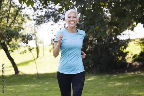 Fototapeta Senior woman jogging through park