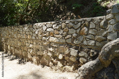 Fototapeta High stone fence along the pedestrian rural path in summer Sunny day