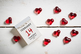 Tear-Off Calendar with Valentine's Day 2019 on top and decorative hearts on wooden background