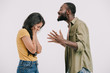 side view of african american boyfriend screaming at girlfriend isolated on white