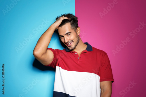 Leinwanddruck Bild Young man with trendy hairstyle posing on color background