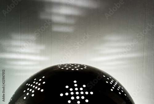 The sun in a colander. Rays of light through the holes - 221867052
