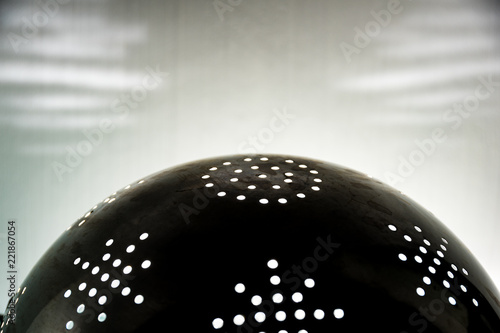 Naklejka The sun in a colander. Rays of light through the holes