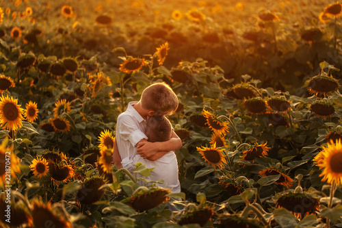 Fototapeta Two cute sibling boys hugging and having fun sunflowers field. Adorable friends together on warm summer day. Brother love concept. Back view
