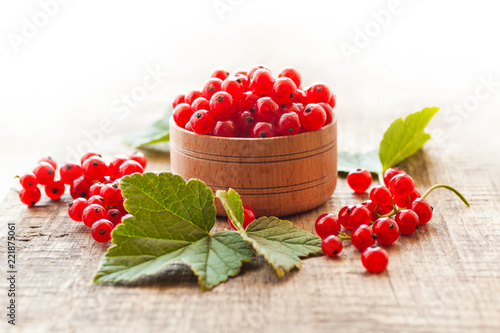 Leinwanddruck Bild Red currant berries in a wooden bowl closeup