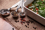 Cooking tools and ingredients concept. Mix of peppers in a metal measuring spoons on on table - 221881867