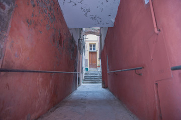 Grungy red walls and alleyway leading to distant step and door © Brian Scantlebury