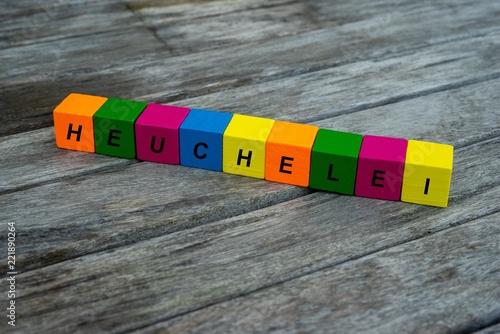 Farbige Holzwürfel mit Buchstaben auf dem das Wort Heuchelei abgebildet ist, Abstrakte Illustration - 221890264