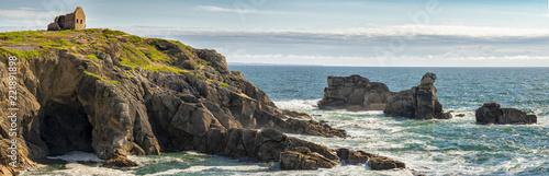un panorama sur un paysage marin avec une maison en ruine sur les bords d'une falaise verte - 221891898