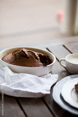 Sticker chocolate cake with cream and cup of milk on wood table