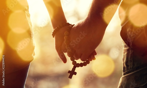 Couple praying together. Holding rosary in hand. - 221894476