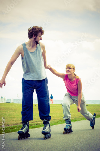 Fototapeta Man encourage woman to do rollerblading