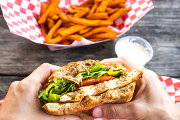 Woman hands hold burger style grilled chicken breast sandwich with lettuce and tomatoes and a side of sweet potato fries