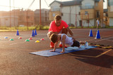 Determinative young football coach learning little boy how to do push ups. Early summer morning training. - 221907849