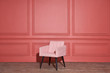 Nice soft pink armchair stands in studio