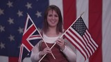 Woman holidng up American Flag and Union Jack Flag as she stands in front of American Flag. - 221908614
