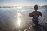Little boy with float life jacket on the beach