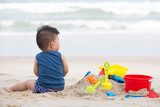 First year old boy play with sand, Taking baby to the beach concept