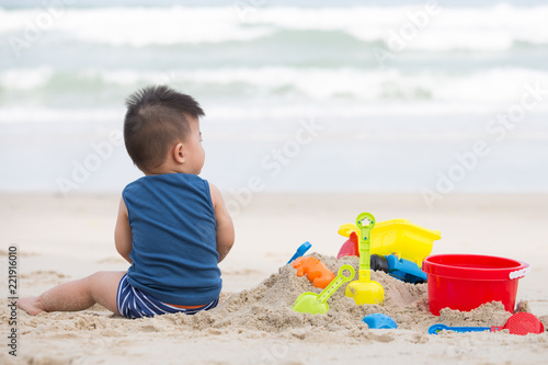 Foto Murales First year old boy play with sand, Taking baby to the beach concept