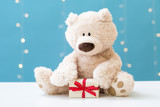 A teddy bear and gift box on a shiny light blue background - 221924877