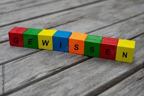Farbige Holzwürfel mit Buchstaben auf dem das Wort Gewissen abgebildet ist, Abstrakte Illustration - 221930270