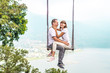 Leinwandbild Motiv Young honeymoon couple swings in the jungle near the lake, Bali island, Indonesia.