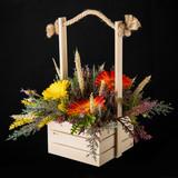 Flowers bouquet arrangement in pine basket on black background.
