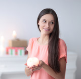 young woman with a decorative candle on a background of a bright living room - 221946801