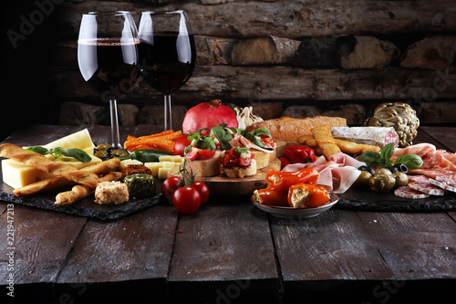 Italian antipasti wine snacks set. Cheese variety, Mediterranean olives, pickles, Prosciutto di Parma, tomatoes, artichokes and wine in glasses - 221947213