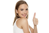 Portrait of young beautiful woman with makeup on white backgeound and showing thumbs up - 221948662