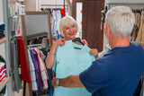 Stunning look. Adorable grey haired woman looking at her husband while keeping a dress at her chest and expressing satisfaction during shopping process - 221950088