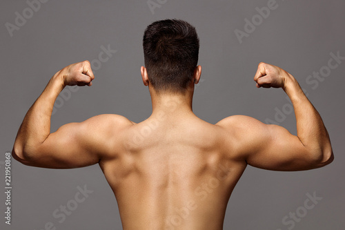 man with muscular body and strong back of bodybuilder athlete with biceps and triceps on grey background, sport and training