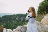 Young woman taking picture of the mountains - 221951436