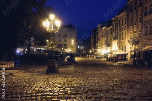 fototapeta na ścianę Old European city pedestrian street night city lights. Old architeccture illuminated street
