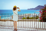 Tourist girl with straw sunhat taking a picture of the mediterranean sea with a smartphone in Altea, Alicante, Spain - 221953445