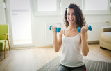 Young attractive sportswoman doing exercises at home - 221953848