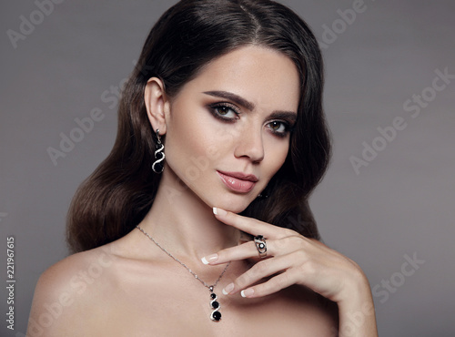 High Fashion brunette model woman in diamond  jewellery set isolated on gray background. Beauty female face, beautiful make-up. Gorgeous lady with elegant wavy hairstyle, studio closeup portrait. © Victoria Andreas