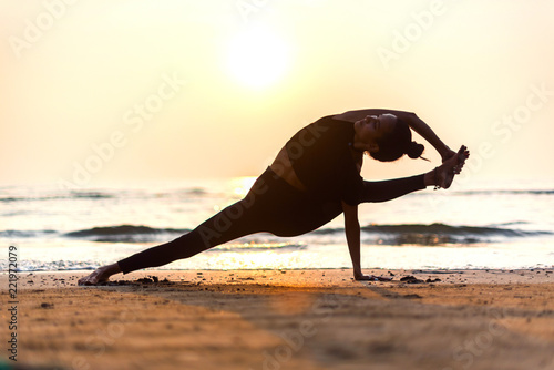 Poster Young healthy woman practicing yoga on the beach at sunset