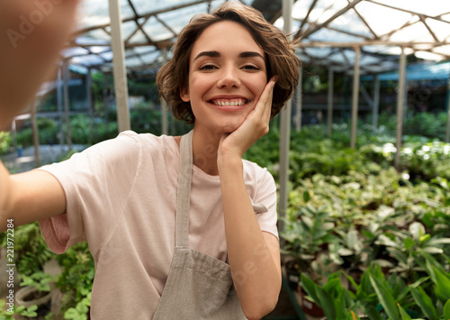 Gardener standing over plants in greenhouse take a selfie by camera. - 221972284