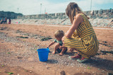 Mother playing with toddler on beach