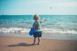 Toddler on the beach throwing stones in the sea
