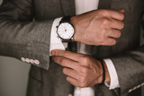 closeup fashion image of luxury watch on wrist of man.body detail of a business man.Man's hand in a grey shirt with cufflinks. Tonal correction  - 221974214