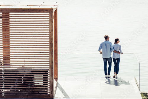 Leinwanddruck Bild high angle view of stylish couple standing on pier near lake at country house