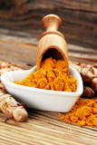 Turmeric powder and fresh turmeric on rustic background - 221981663