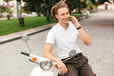 Smiling curly business man talking by smartphone and looking away