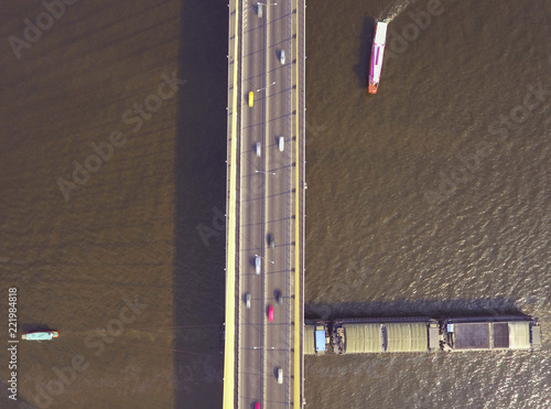 Fridge magnet RAMA VIII bridge across Chao Phraya river at Bangkok Thailand aerial top down shot in bright after noon day light with passenger boat and tourist floating restaurant in the river